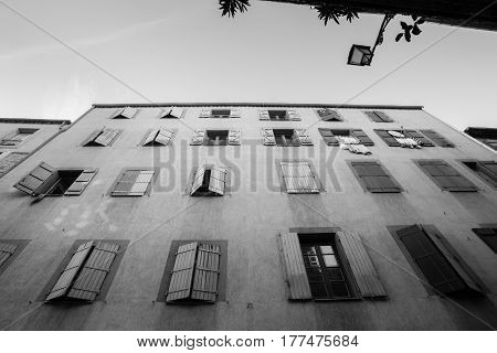 Exterior wall with many windows and shutters building and architecture Narbonne France in monochrome