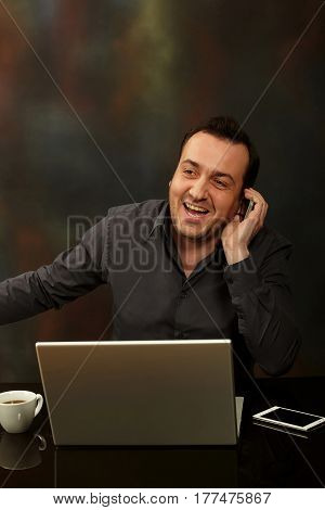 Businessman working on a laptop and talking to a mobile phone.
