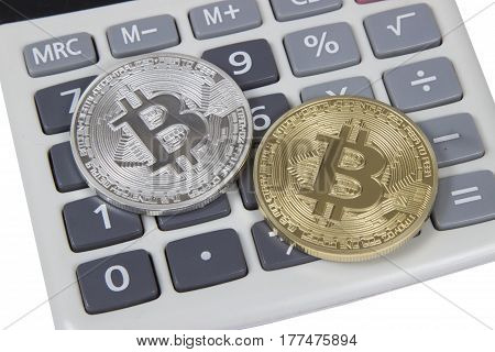 gold and silver bitcoin lies on a white calculator. electronic money and cryptocurrency