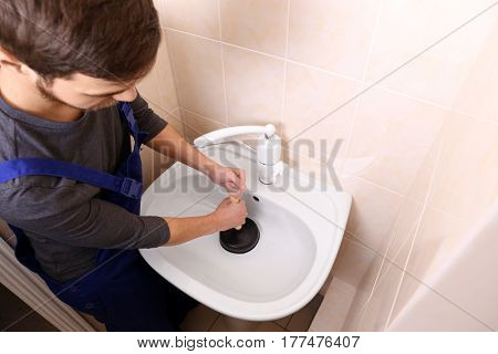 Plumber repairing sink with hand plunger