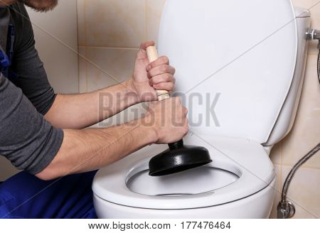 Plumber repairing toilet with hand plunger
