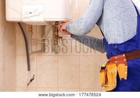 Plumber repairing boiler in bathroom