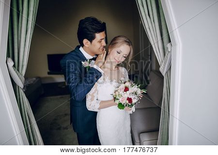 Bride in wedding dress and the groom in a wedding suit Idoma people standing near curtains