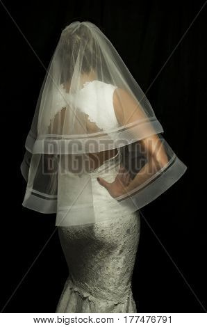Portrait of a beautiful girl in image of the bride. Photo shot in the Studio on a black background