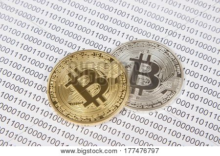gold and silver bitcoin on the background of binary code. electronic money and cryptocurrency
