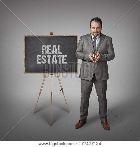 Real estate text on  blackboard with businessman and golden egg