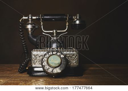 Vintage silver  telephone on a  wooden table..