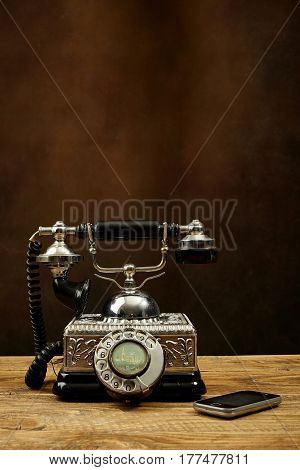 Vintage telephone on wooden table and a mobile phone.