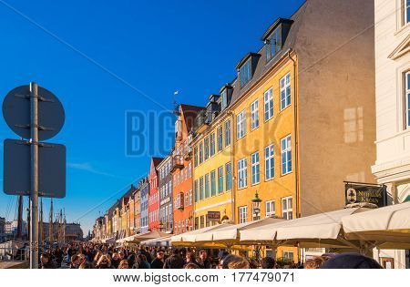 COPENHAGEN DENMARK - MARCH 11 2017: Tourists in Copenhagen Nyhavn district promenade with its colorful facades 17th century waterfront is an entertainment district and famous landmark