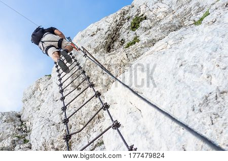 Crawling man in mountains, Man on ladder in mountains, dangerous stretch on rock, ferrata crawling man in mountains