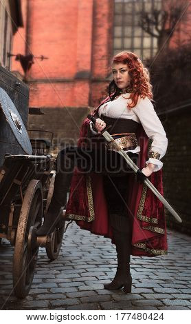 Warrior woman with sword in medieval clothes on the street is very dangerous