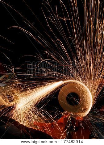 Cutting metal with electric grinder. Flying glowing sparks on dark background