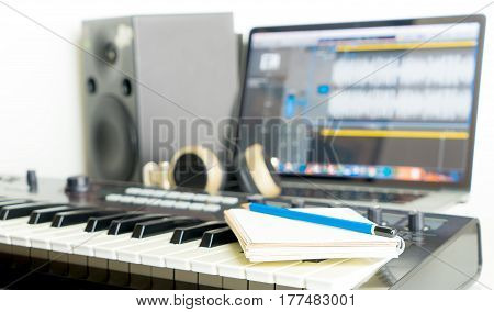 Notebook and Music Keyboard on Music studio working desktop for song writer