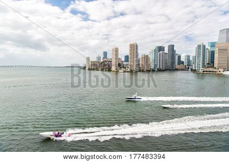 Miami, USA-February 19, 2017 : Aerial view of Miami skyscrapers with blue cloudy skywhite boat sailing next to Miami downtown