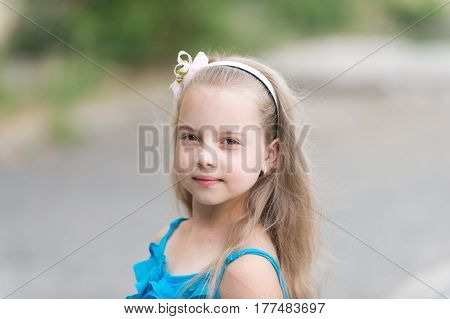 Small Baby Girl With Adorable Face In Blue Vest Outdoor