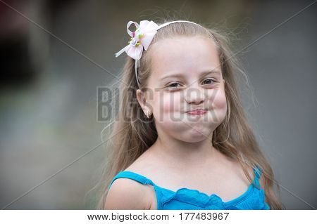 Small Baby Girl With Smiling Face In Blue Vest Outdoor