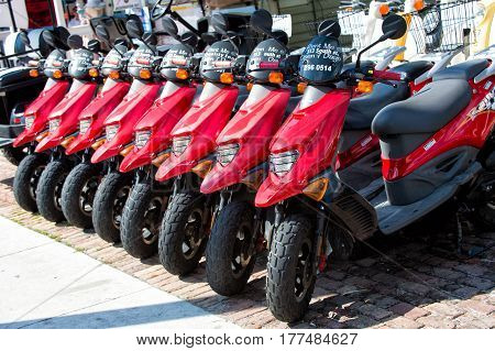 Key West Florida - January 09 2016: red scooters or motorcycles for sale or hire standing in row with wheels and lights sunny day outdoor hiring transportation traveling