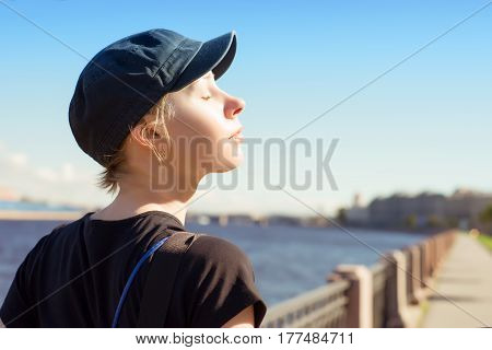 Young relaxing woman at sunny day against summer city landscape. Blue cap eyes closed river at background