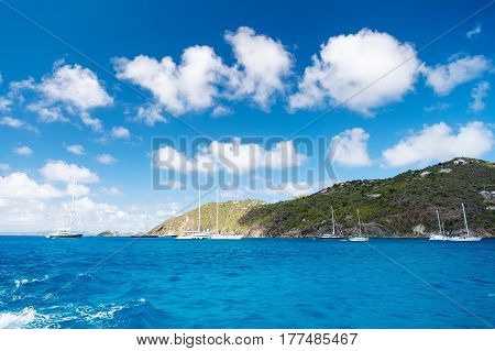 green mountain with yacht boat ship transportation in bay or harbor with sea ocean water and blue cloudy sky sunny summer as natural background. traveling and vacation yachting