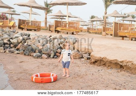 Small Baby Boy With Adorable Face With Lifebelt On Beach