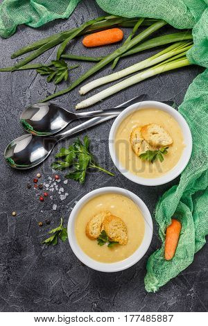 Two bowls of vegetable soup puree with croutons and vegetables in the background. Top view