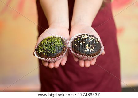 chocolate cupcakes with sprinkles in hands of small baby or child in red chef or cook apron holding homemade pastry muffins on blurred background cooking food