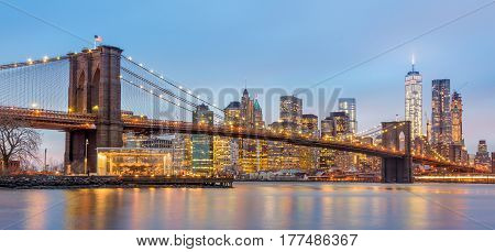 Brooklyn bridge and New York City Manhattan downtown skyline at dusk with skyscrapers illuminated over East River panorama. Panoramic composition.