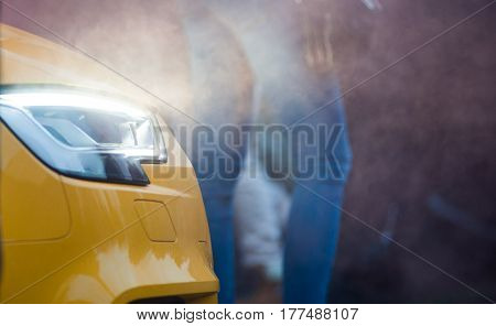 front view of a luxury car close up with lights on and smokey on the background