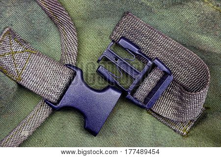 Black plastic carabiner on a green backpack