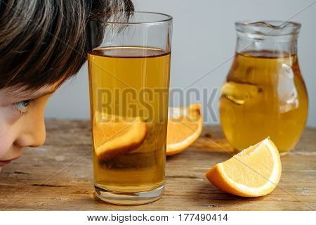 Funny Boy With Homemade Kombucha In A Decanter With Orange  On A Wooden Table.