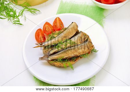 Appetizing sandwiches with sprats on white plate