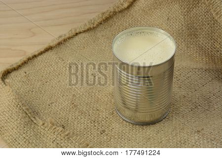 Canned evaporated milk in open can on burlap