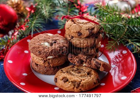 Dark and White  Chocolate Chip Cookies and a Branch of decorated Christmas Tree on the background. Holiday treat.