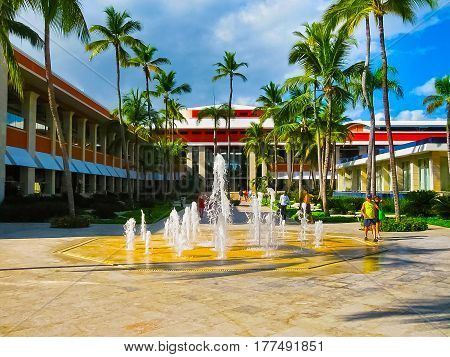 Punta Cana, Dominican republic - February 04, 2013: Ordinary tourists resting in Barcelo Bavaro Beach hotel with fountain under palms near the beach