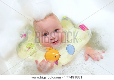 Bathing a small child in a bubble bath.