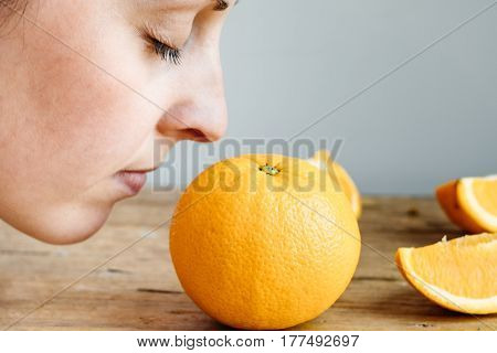 Woman Smelling Fresh Orange On Wooden Background