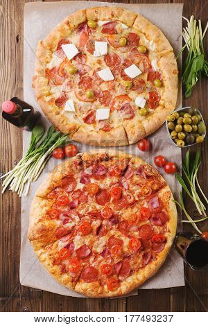Rustic pizza with salami mozzarellabasil top view with copy space. Two pizzas on a wooden table. Pizza salami on wooden background. Pizza salami with tomatoes and olives