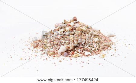 heap of different cockshells and pink sand over white background