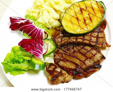 Grilled t bone steak meal with mashed potato, lettuce salad and grilled squash slice.