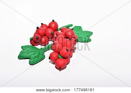 Red currant made from plasticine. Isolated on white background.