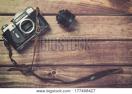 Old film camera with strap and lens on wooden background. Vintage toned and top view with free space.