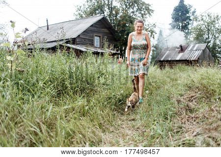 Authentic rural picture of walking cat, woman, and old log house with heating bath.