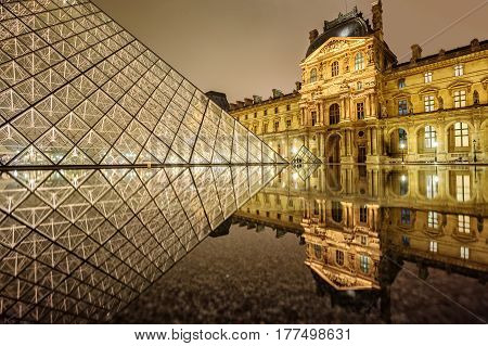 PARIS FRANCE - DECEMBER 31: Louvre museum and glass Pyramid illuminated by night. With over 8 million visitors pro year Louvre is one of the world's largest museums. Paris France on December 31 2013