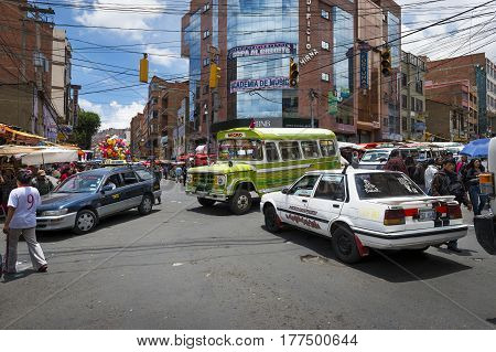 La Paz Bolivia - December 8 2013: Busy intersection with cars buses and people in the city of La Paz in Bolivia.