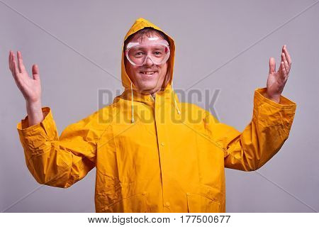 A middle aged man in a yellow raincoat and safety glasses feeling happy and laughing