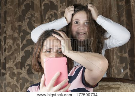 Mother And Daughter In Living Room Arguing And Holding Tablet