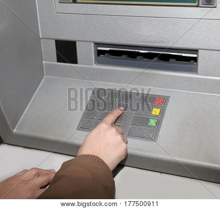 hand typing a PIN into the keypad of an ATM to withdraw money