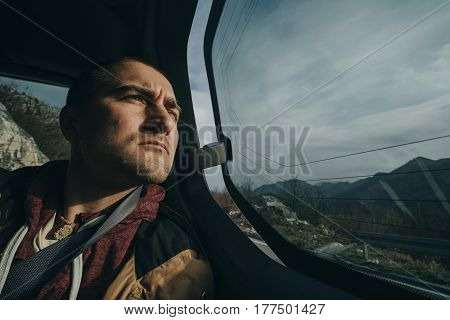 Young man driving in car in mountains. Road trip