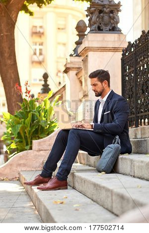 A handsome young businessman sitting on the stairs and using his laptop at the Basilica in Budapest, Hungary.