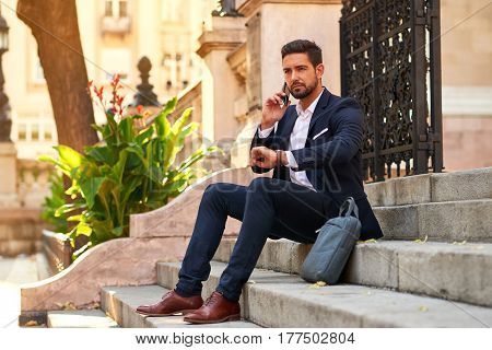 A handsome young businessman sitting on the stairs talking on his smartphone and checking the time on his watch at the Basilica in Budapest Hungary.